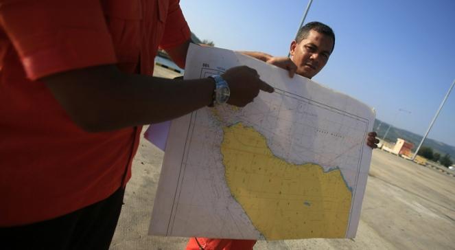 Ratownicy pokazują na mapie rejon, w którym zniknął samolot